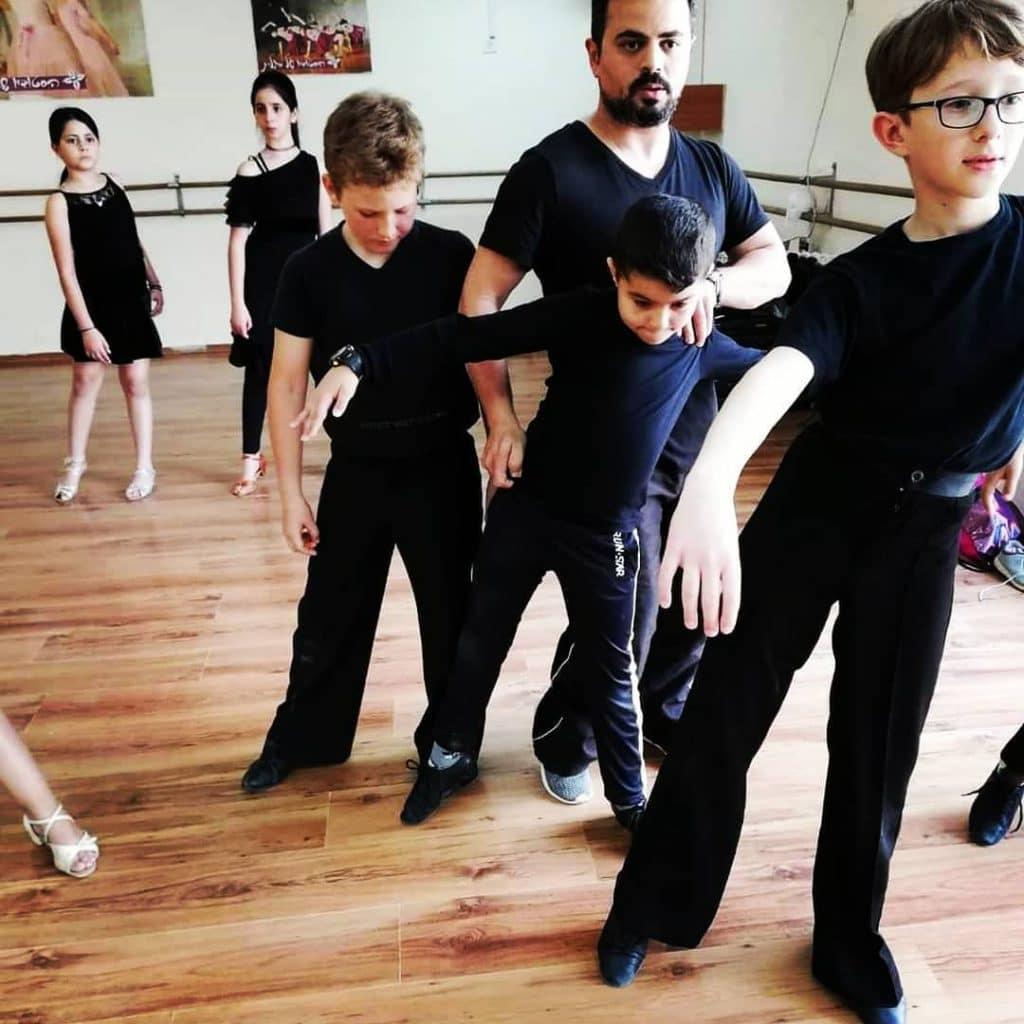 מורה לריקוד בזמן שיעור עם תלמידיו בחוג ריקודים סלוניים ולטיניים לילדים