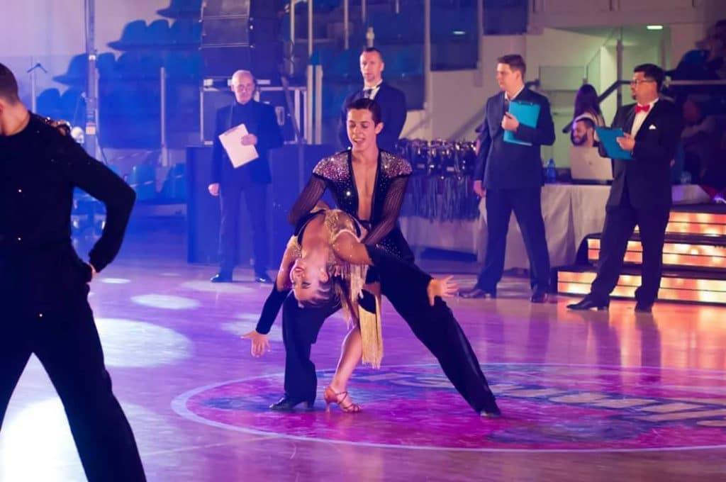 זוג נערים בוגרי חוג ריקודים סלוניים ולטיניים לילדים בריקוד סמבה בתחרות ריקודים