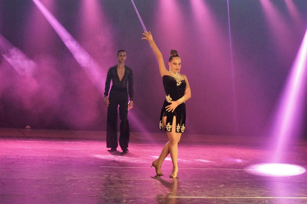זוג רקדנים מתבגרים בוגרי חוג ריקודים סלוניים ולטיניים לילדים בריקוד על הבמה