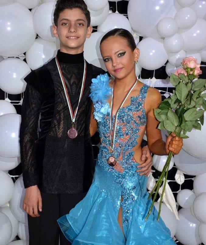 רקדנית ורקדן ריקודים סלוניים ולטיניים עם מדליות ניצחון לאחר תחרות