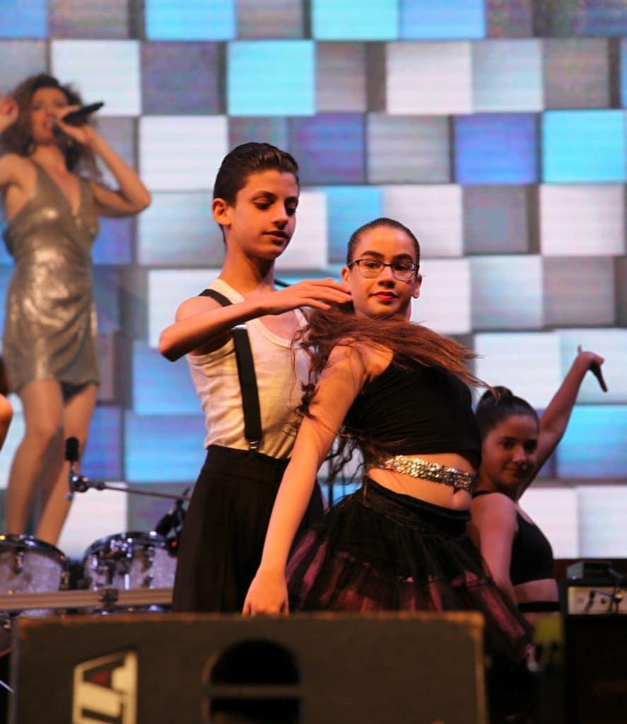 זוג רקדנים צעיר במופעי ריקוד עירוניים על בימת מודיעין