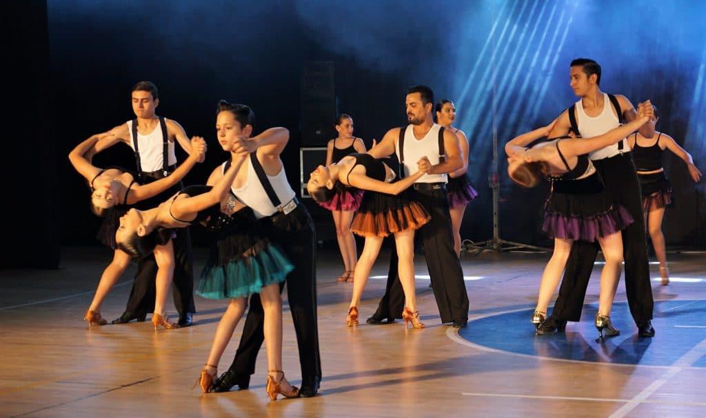 זוגות בני נוער רוקדים על הבמה במופעי ריקוד סלוניים ולטיניים
