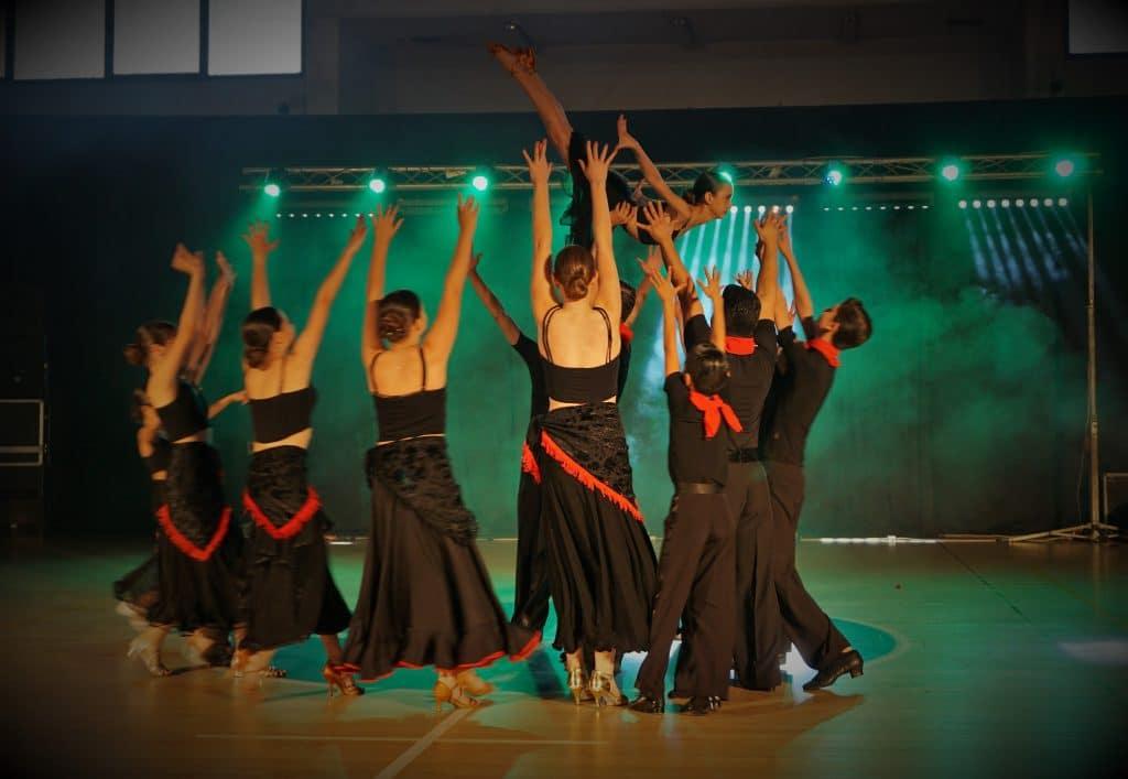 תלמידי בית הספר בריקוד פותח של מופעי ריקוד סלוניים ולטיניים