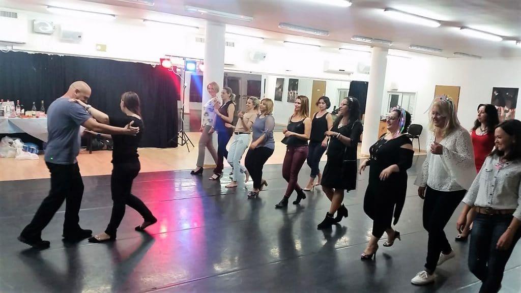 מדריכה מדגימה צעדים חדשים בחוג ריקודים סלוניים ולטיניים למבוגרים