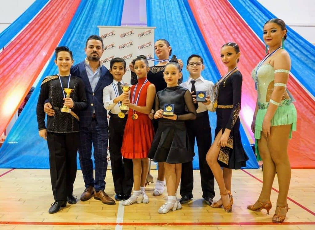 רקדנים שזכו בתחרות ריקודים סלוניים ולטיניים ומנהל בית הספר אבי צור
